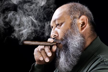 Fond de commerce du m�le adulte � long cigare fumer barbe sur fond sombre Banque d'images