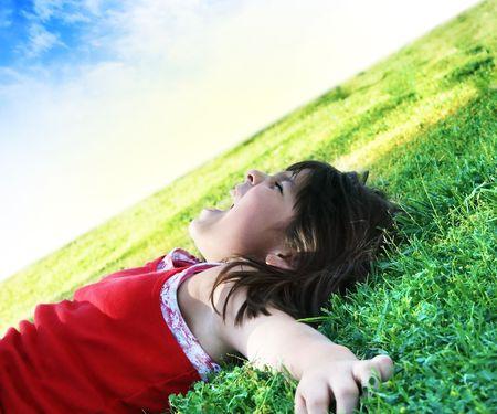 lying in grass: Imagen de existencias de ni�a peque�a puesta sobre c�sped en un d�a perfecto