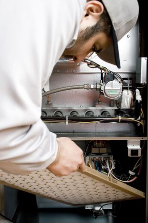 Stock image of HVAC technician replacing filter on furnace