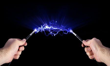 Stock beeld van handen houden van levende elektrische kabels  Stockfoto