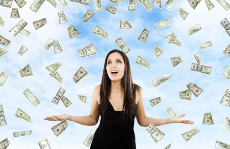Stock image of woman standing with open arms amidst falling money photo