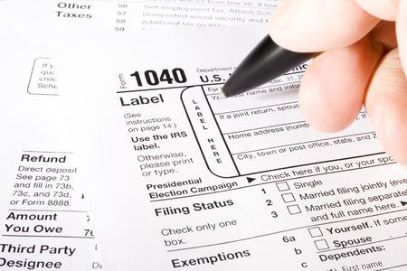 filling out: Stock image of man filling out 1040 Tax form