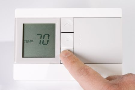 Stock image of hand adjusting thermostat photo