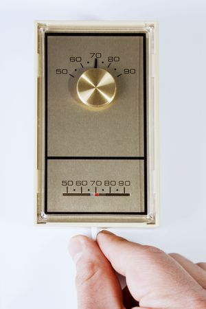 Stock image of hand adjusting thermostat