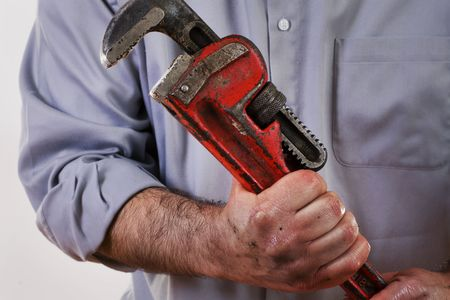 Stock image of plumber in uniform holding pipe wrench. photo