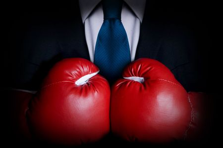 takeover: Stock image of person wearing business suit and boxing gloves Stock Photo