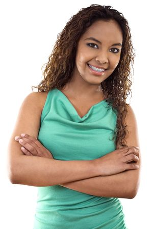 Stock image of female with braces standing with her arms crossed, over white background.