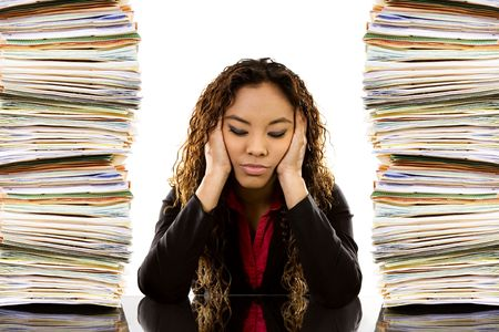 Stock image of woman sitting at desk with a pile of paperwork on each side