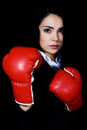 Stock image of businesswoman in fighting stance wearing boxing gloves over black background