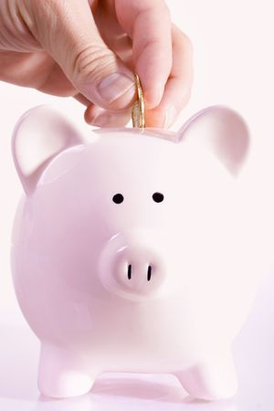 money box: Stock image of man depositing a coin in a piggy bank Stock Photo
