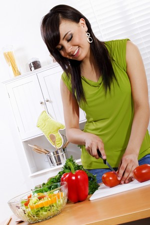 Stock image of woman in kitchen preparing a fresh vegetable salad photo