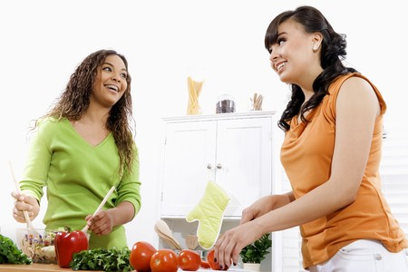 Stock image of two young women in kitchen preparing a salad  Stock Photo