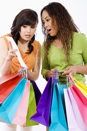 Stock image of two surprised young women looking at sale ticket after shopping too much photo