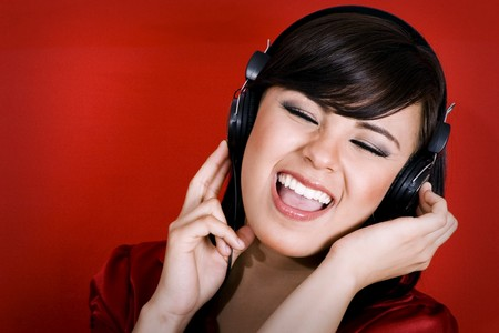 Stock image of woman wearing headphones, Listening to music and singing over red background. photo