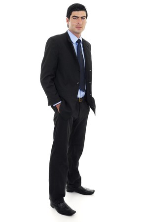 Stock image of businessman standing with arms on pockets over white background. Full body shot.