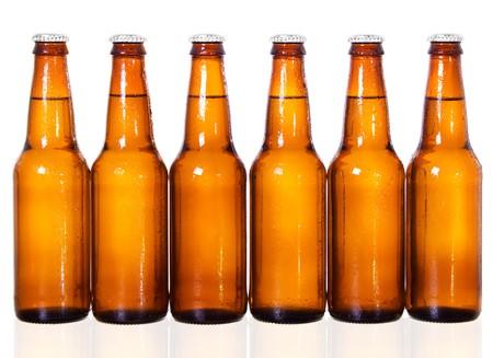 Stock beeld van zes donker bier flessen op witte achtergrond met reflectie op bodem