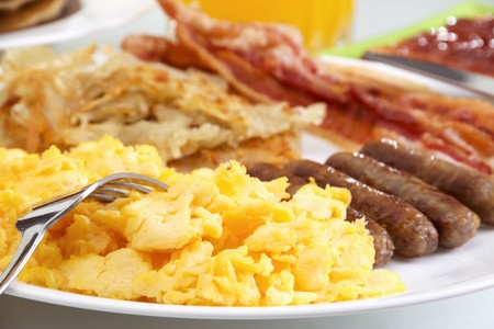 scrambled: Stock image of hearty breakfast, focus on foreground.  Stock Photo