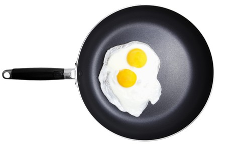 Stock image of a pair of fried sunny side up eggs on skillet isolated on white Stock Photo - 7860657