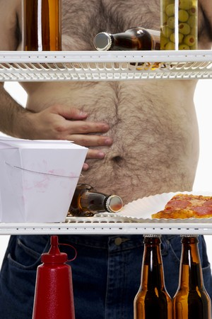 Stock image of hungry overweight man looking for a snack on his refrigerator photo
