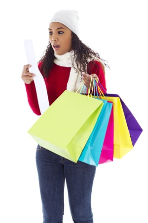 Stock image of surprised woman looking at ticket. Holding colorful shopping bags.