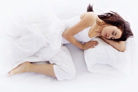 Stock Bild junge Frau auf weiß Bett schlafen
