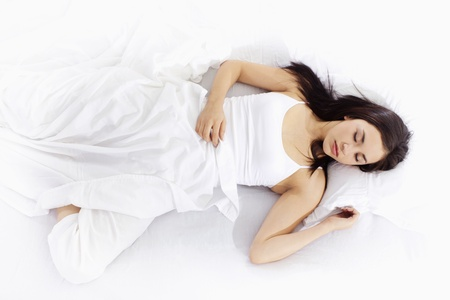 lying on side: Stock image of young woman sleeping on white bed Stock Photo