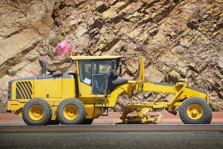Stock image of motor grader working on road construction photo