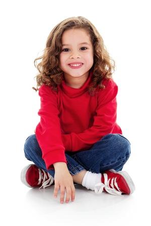 Stock foto van schattige kleine meisje zitten en glimlachen, geïsoleerd op wit met schaduw op de vloer