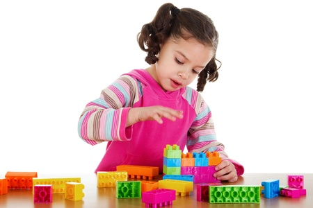 Stock image of little girl playing with construction blocks over white background