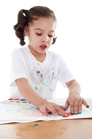 Stock image of child finger painting with watercolors over white background photo