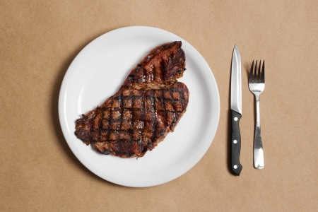 paper plates: Stock image of steak dinner with knife and fork sparse composition Stock Photo