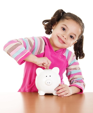 Stock image of little girl placing coin in piggy bank over white background