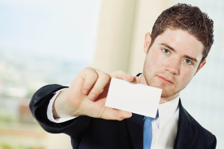 Stock image of caucasian businessman showing business card