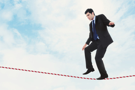 ideas risk: Stock image of businessman walking the tightrope