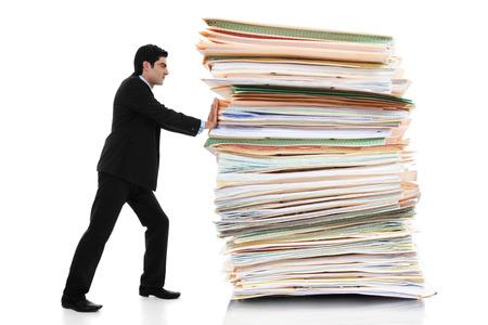 Stock beeld van zakenman duwen een gigantische stapel documenten op een witte achtergrond