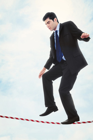 Stock image of businessman walking the tightrope photo