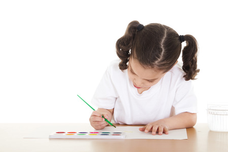 Stock image of female preschooler drawing with watercolors over white background