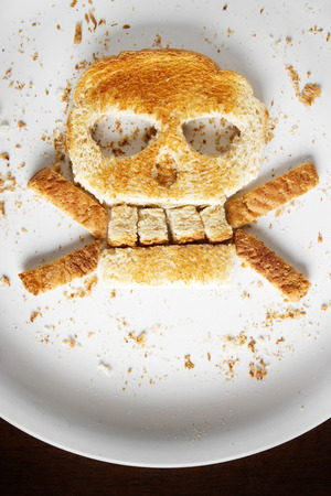 Stock image of bread skull and crossbones on white plate photo