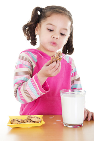 Stock image of little girl eating chocolate chip cookies and milk over white background