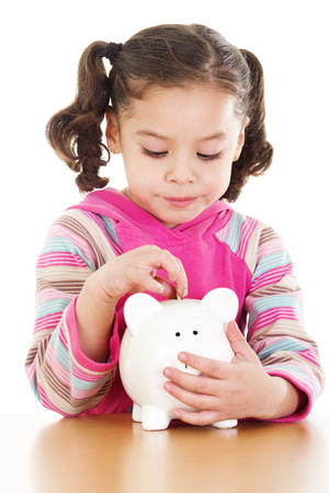 Stock image of little girl saving coin on her piggy bank over white background