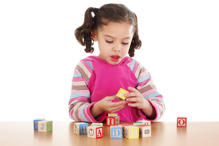 Stock image of child playing with cube letters over white background
