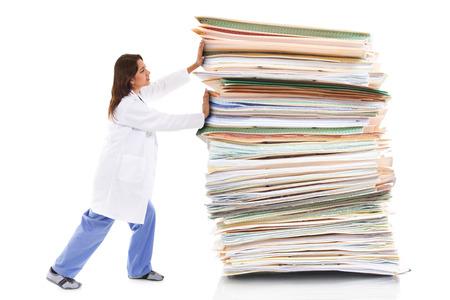 Stock beeld van een vrouwelijke gezondheidszorg werknemer het duwen van een gigantische stapel papieren op een witte achtergrond Stockfoto