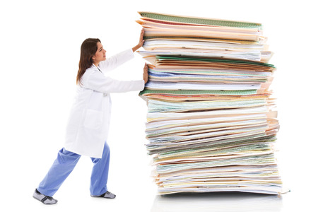 Stock image of a female healthcare worker pushing a giant stack of papers isolated on white background Standard-Bild