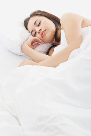 Stock image of woman sleeping in bed, white bedding photo