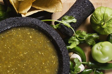 Stock image of mexican salsa verde on mortar and pestle with ingredients Zdjęcie Seryjne - 73346364