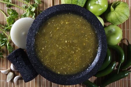 husk tomato: Stock image of mexican salsa verde on mortar and pestle with ingredients
