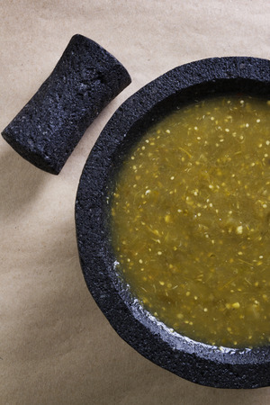 husk tomato: Stock image of mexican salsa verde on mortar and pestle