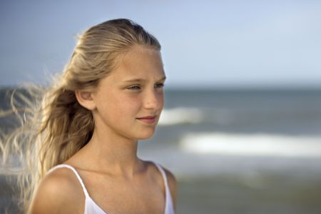 bald girl: Portrait of pre-teen girl on beach with ocean waves in background.