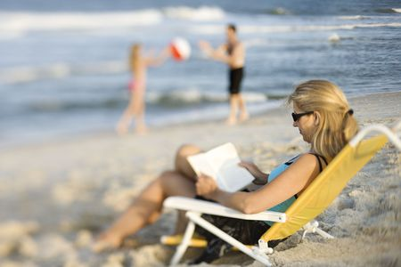 Caucasian mother reading in lounge chair on beach while husband and daughter play ball in background. photo