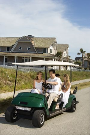 Caucasian family of four driving golf cart down residential street. Stock Photo - 1762088